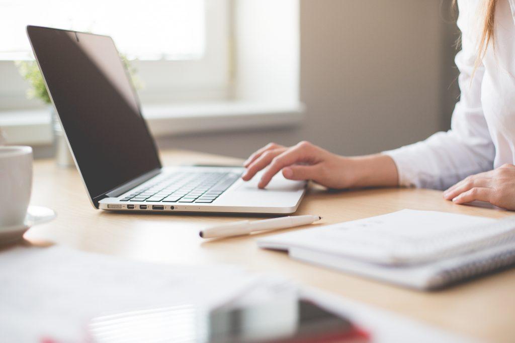 women's hands working on laptop computer