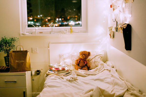 teddy bear in child's bed with white christmas lights