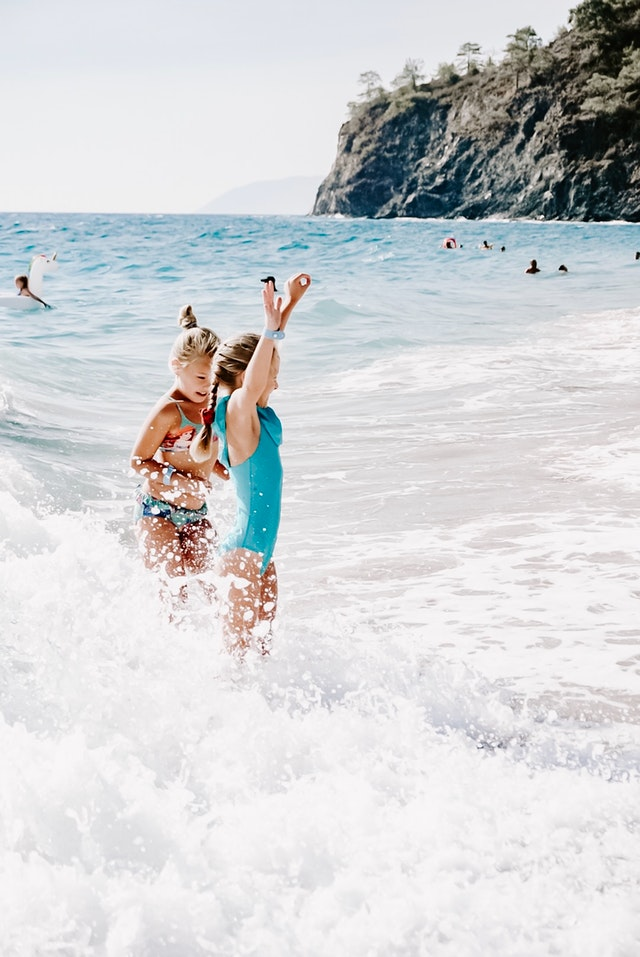 girls playing in the ocean and waves