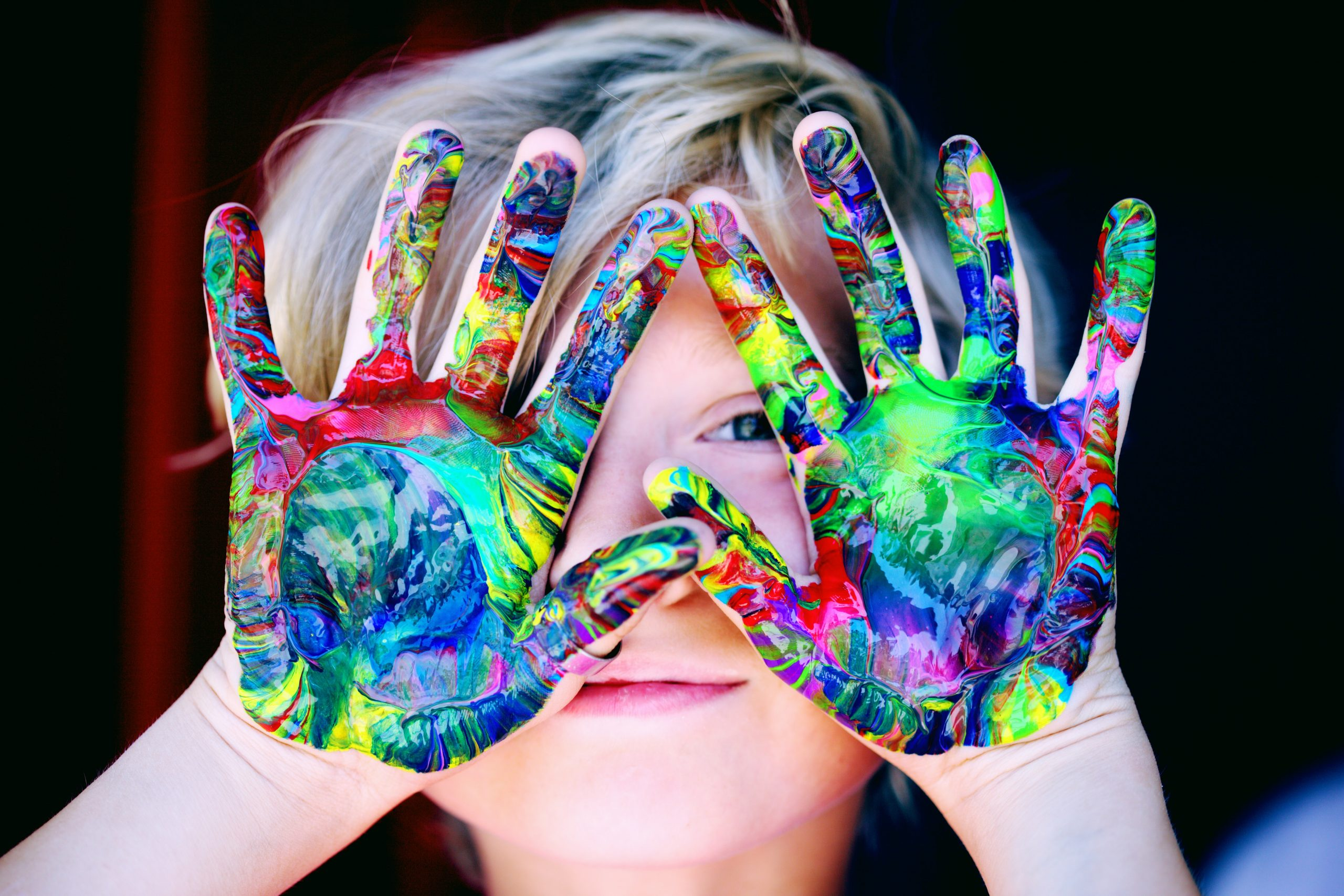 smiling child showing hands covered in paint