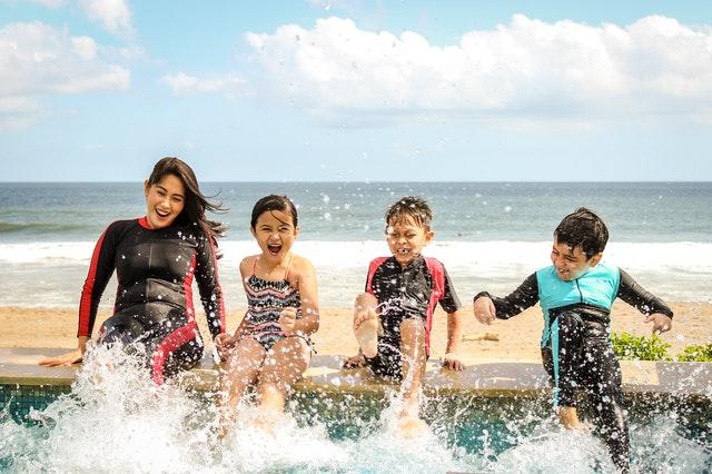happy family splashing water by the beach